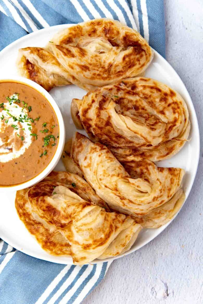 Freshly made flaky roti canai served on a plate with a curry on the side