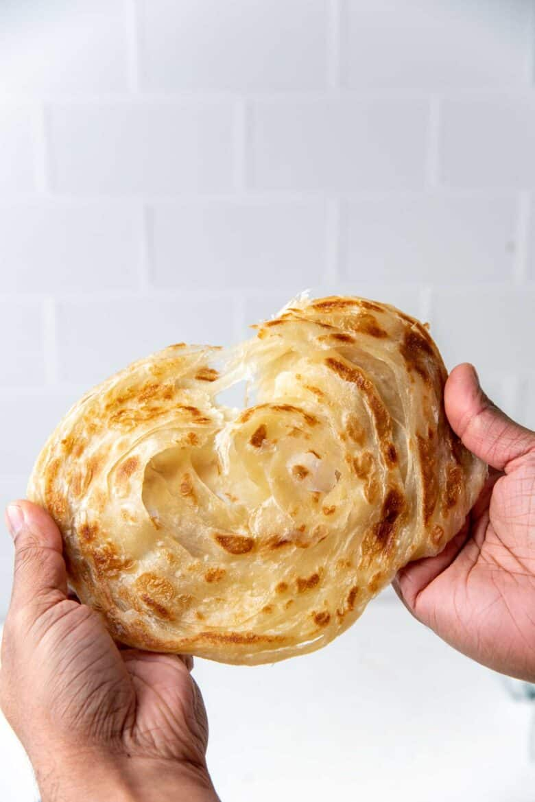 Flaky roti paratha, being pulled apart